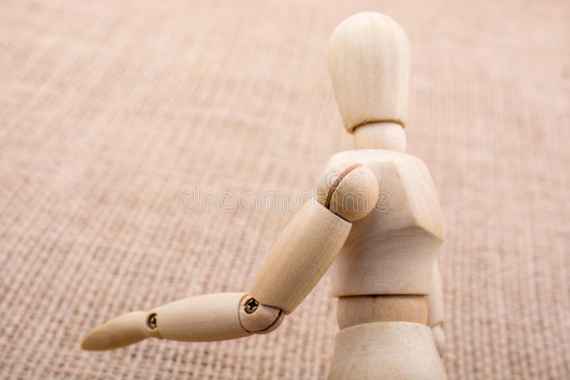Wooden dolls posing on canvas. Wooden dolls of a man posing on canvas royalty free stock photography