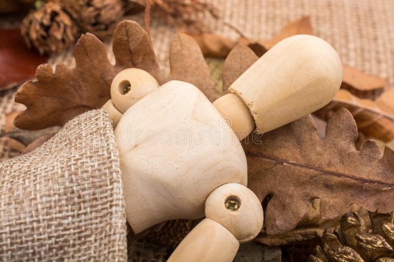 Wooden dolls posing amid leaves. Wooden dolls posing amid autumn background royalty free stock photo