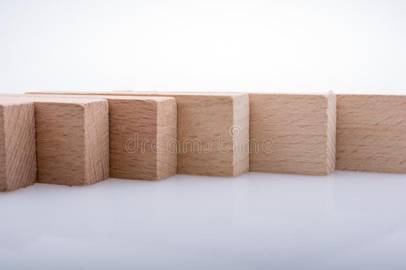 Wooden domino blocks on white background. Wooden Domino Blocks in a line on a white background royalty free stock image