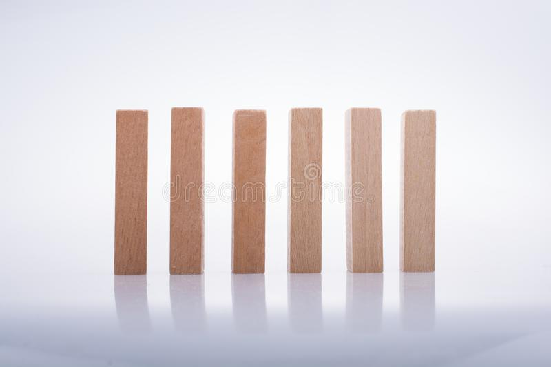 Wooden domino blocks on white background. Wooden Domino Blocks in a line on a white background stock photography