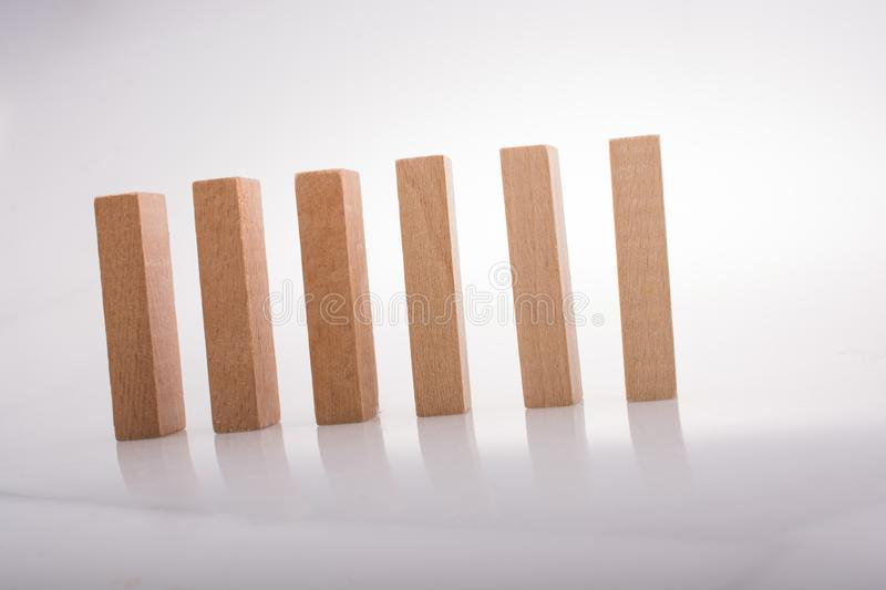 Wooden domino blocks on white background. Wooden Domino Blocks in a line on a white background stock photo