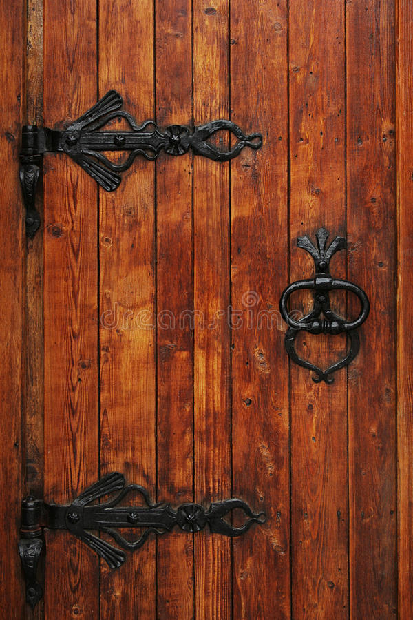 Wooden door with the beautiful iron handle royalty free stock photography