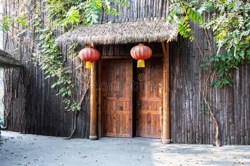 Wooden door in a wooden building. Chinese big red lanterns hang in front of the entrance. Bamboo visor above the entrance. Wooden door in a wooden building royalty free stock photography