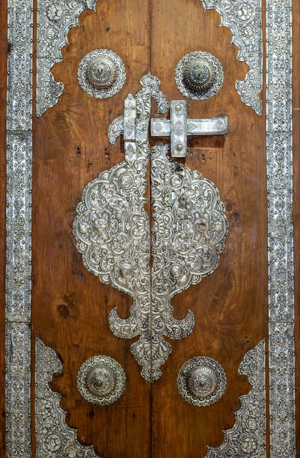 Wooden door decorated with silver plating ornaments from Sayeda Zaynap Mosque, Cairo, Egypt stock images