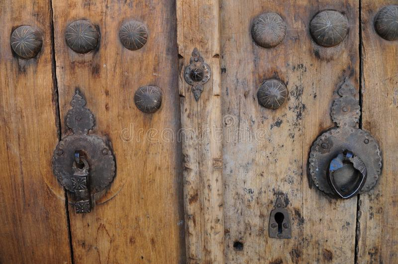 Wooden door with different knockers of ancient mud houses in Abyaneh, Iran. Wooden door with different knocker of ancient mud houses in Abyaneh, Iran. Two stock image