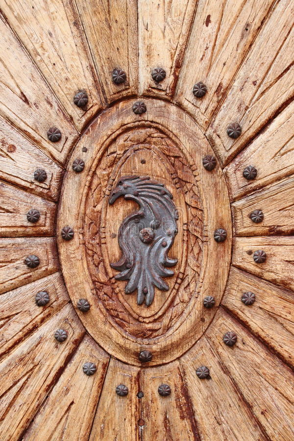 Wooden door with emblem. Detailed view of a wooden door with emblem stock photos