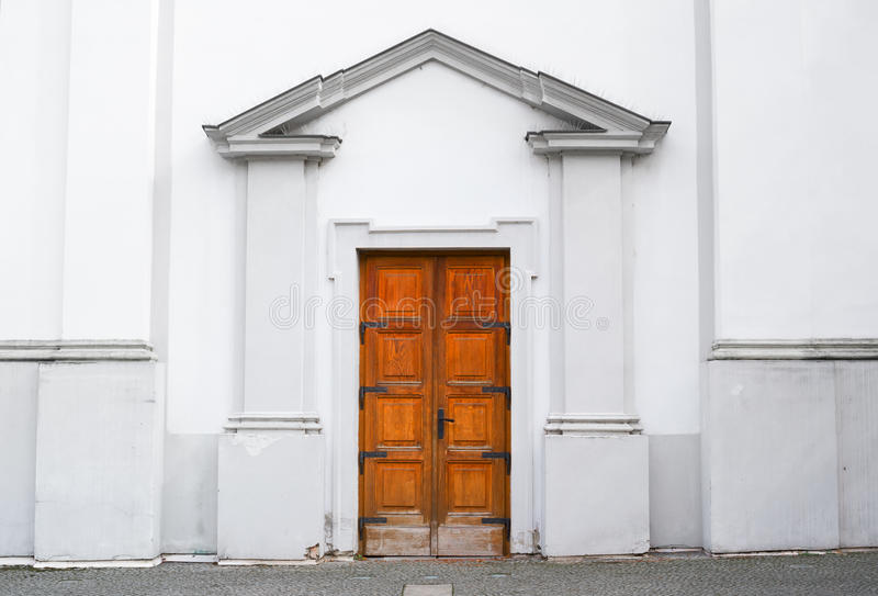 Wooden door and entrance into old historical building. White architecture is made in classicist architectonic style. Symmetrical central composition royalty free stock photos