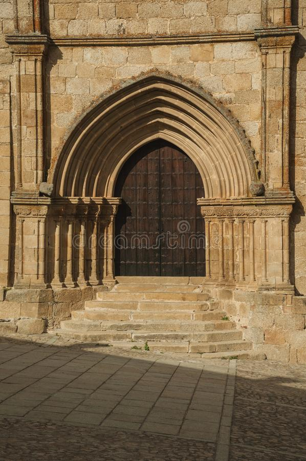 Wooden door with labored medieval stone arches and steps at Trujillo. Big wooden door with labored medieval stone arches and steps on the Santa Maria la Mayor stock images