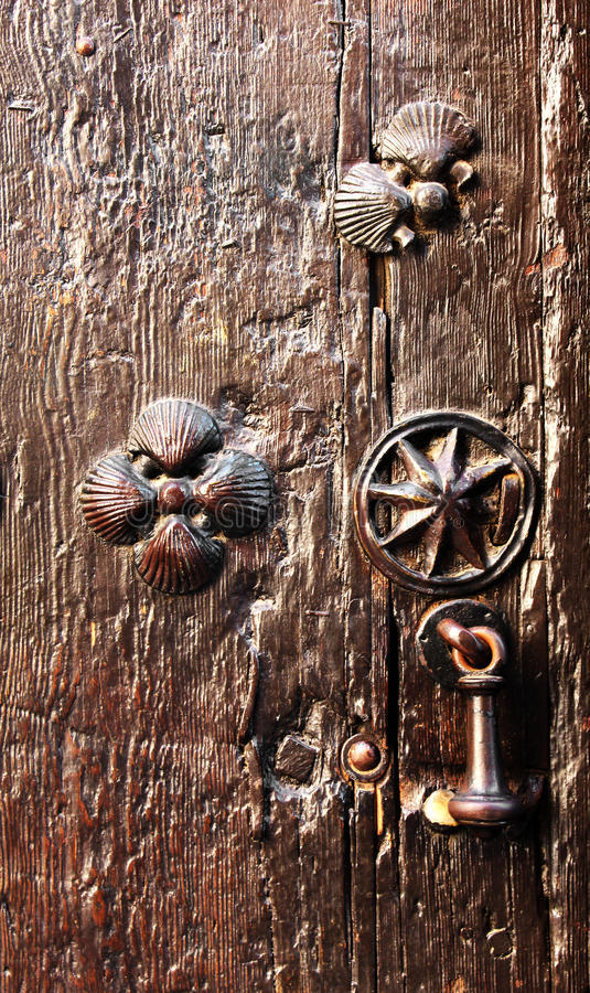 Wooden door with pilgrims scallops and knocker. A detail of a wooden door with pilgrims scallops, nearby the cathedral of toledo, spain, portrait cut stock photos