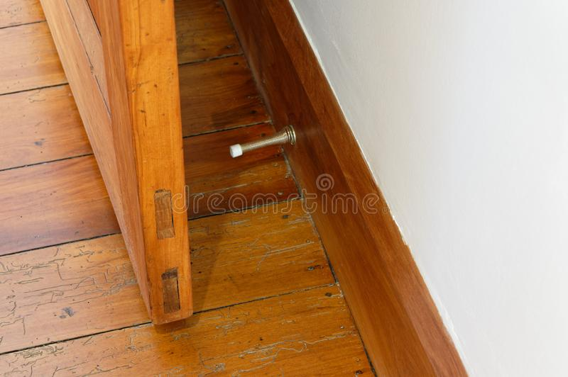 A wooden door is prevented from hitting a white wall by the metal spring door stopper that is attached to the wooden skirting. A spring door stopper is attached stock photography