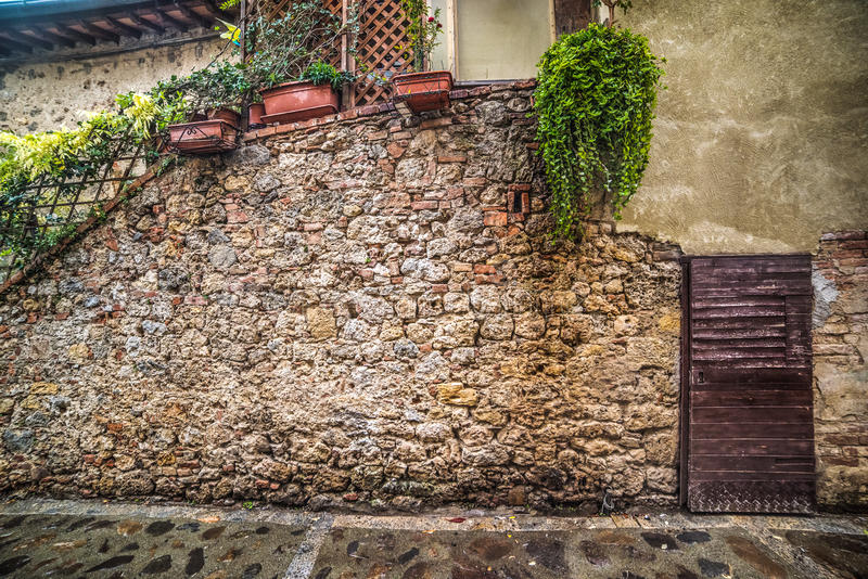 Wooden door in a rustic corner in Monteriggioni. Italy. Public place outdoors royalty free stock photography