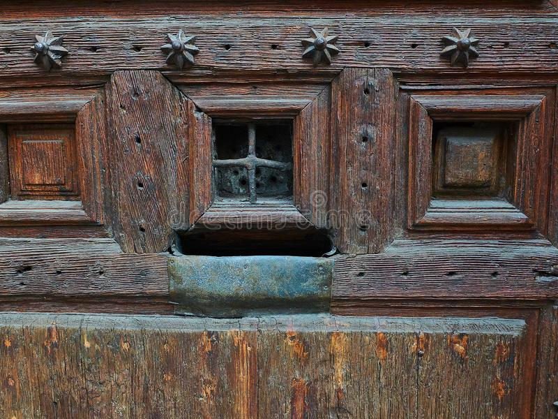 Wooden door with a rusty metal mailbox and a peephole. Antique wooden door with a rusty metal mailbox and a peephole stock images