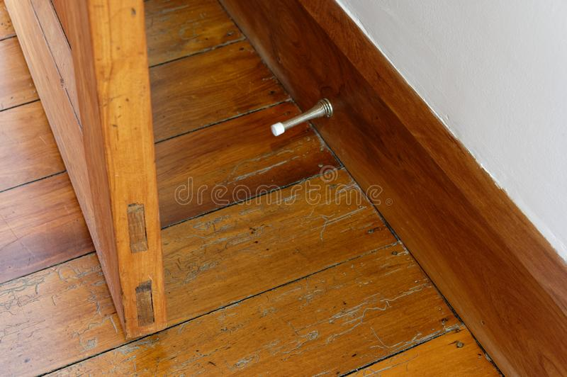 A wooden door is shown with a metal spring door stopper mounted on the skirting board. A wooden door is prevented from striking the wall by a metal spring door royalty free stock image