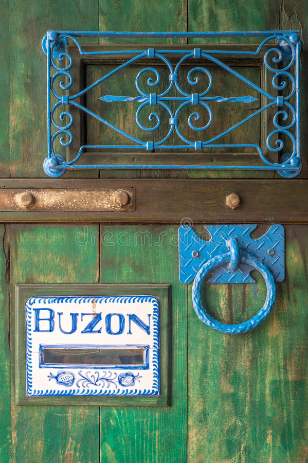 Wooden door with a slot mailbox. And the word in Spanish means box royalty free stock photo