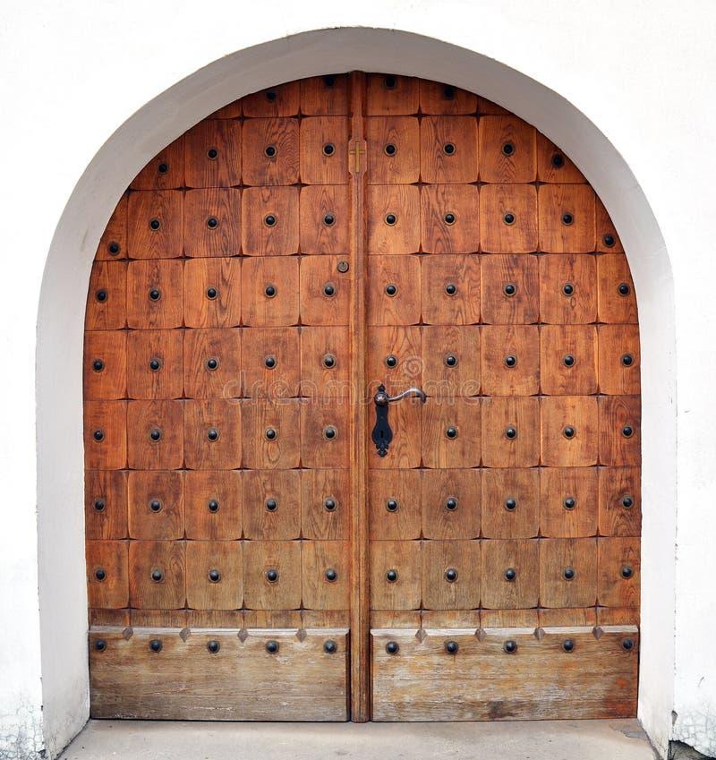Wooden door with smith work. Wooden church door with a proper smith work stock photos