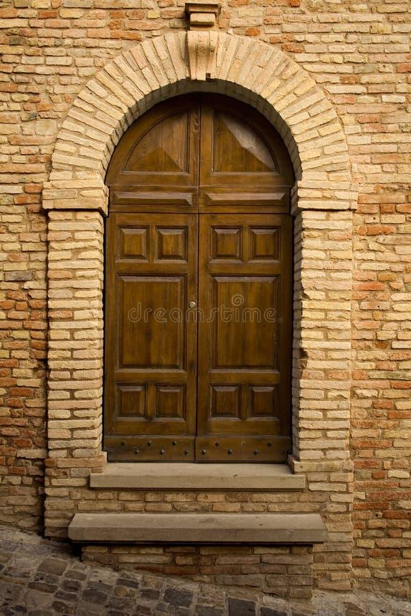 Wooden door in stone archway stock photo