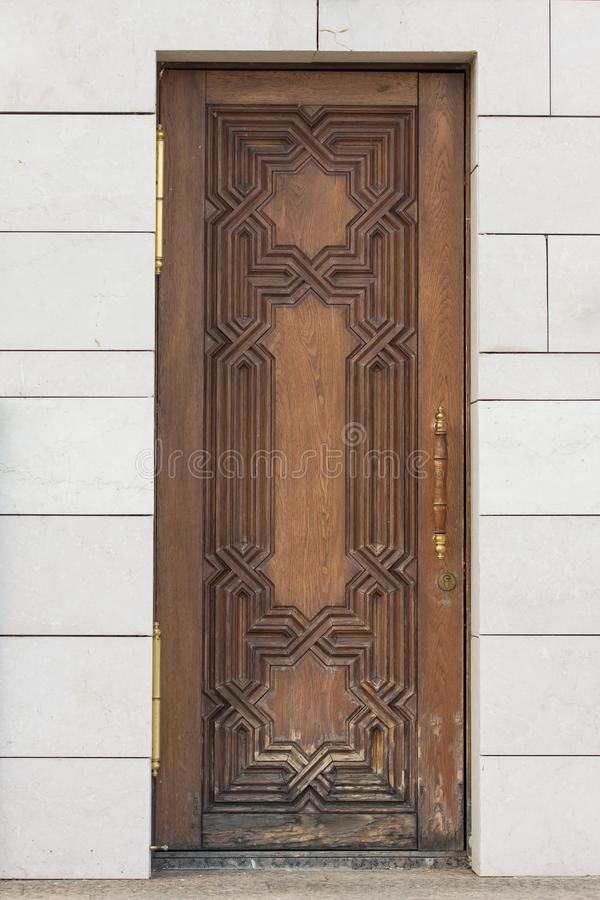 A closed wooden door on a white wall. royalty free stock photography