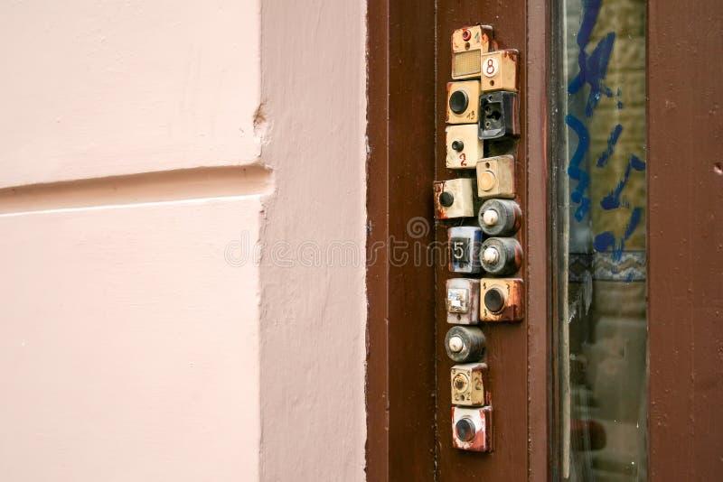Wooden door with a variety of door bells on it royalty free stock photos