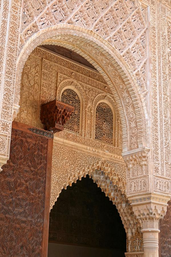 Arch of Palacio de Comares  at Nasrid palace  at the Alhambra in Granada, Andalusia. Wooden door and wall decorations with arabesque ornaments at the Palacio De stock images