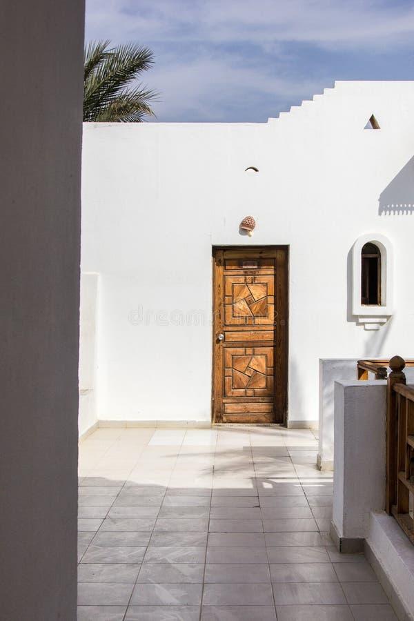 Wooden door in white building at resort. In Egypt stock photo