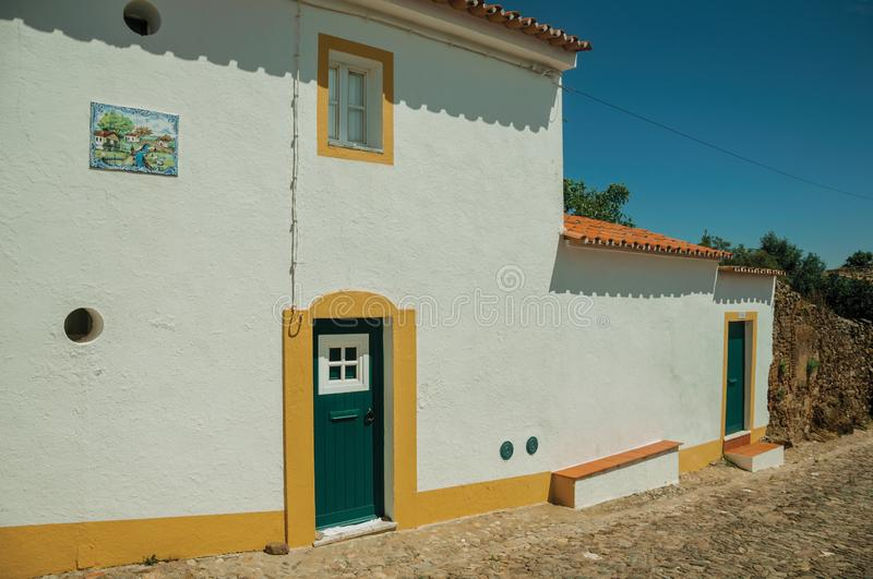 Wooden doors in a house from a street of Evoramonte. Evoramonte, Portugal - July 6, 2018. Green wooden doors in white wall house, from a street of Evoramonte. A royalty free stock image