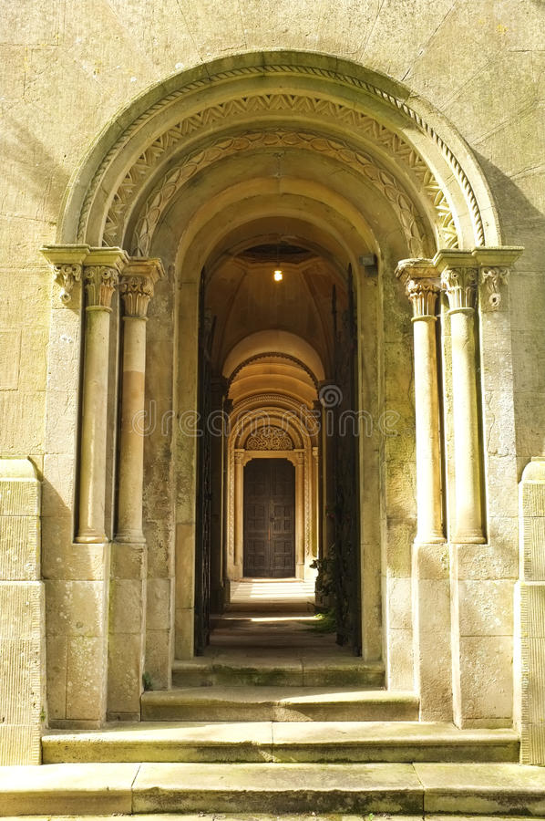 Wooden Door way through stone arches. A wooden door through columned arches of an old church. Decorative and architectural romanesque detail in stone and wood stock photos