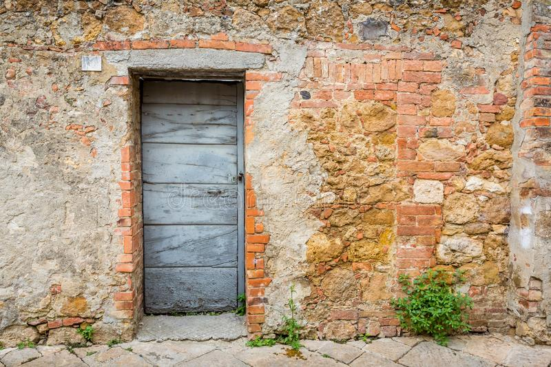 Wooden doorway in stone wall in Tuscany, Italy royalty free stock photos