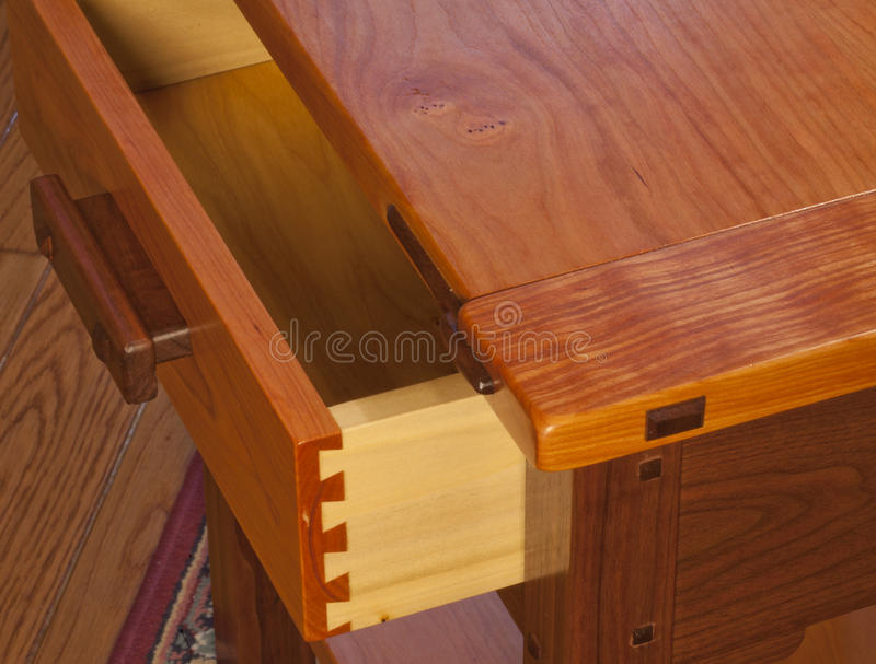 Wooden Dovetail Joinery. Dovetail joinery in the drawer of a handmade cherry, walnut and poplar wood end-table, designed in the Greene & Greene style. Photo made stock images