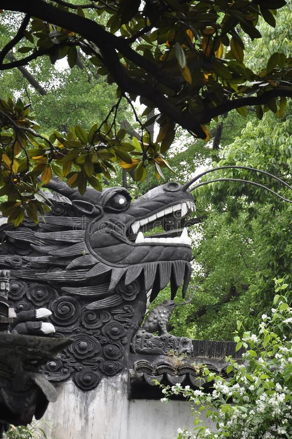 Wooden Dragon head sculpture on the top of the wall in the famous Yu Garden on downtown of Shanghai stock images