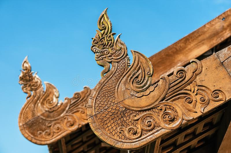 Wooden dragons carved decoration on the roof of buddhist temple, Thailand. stock image