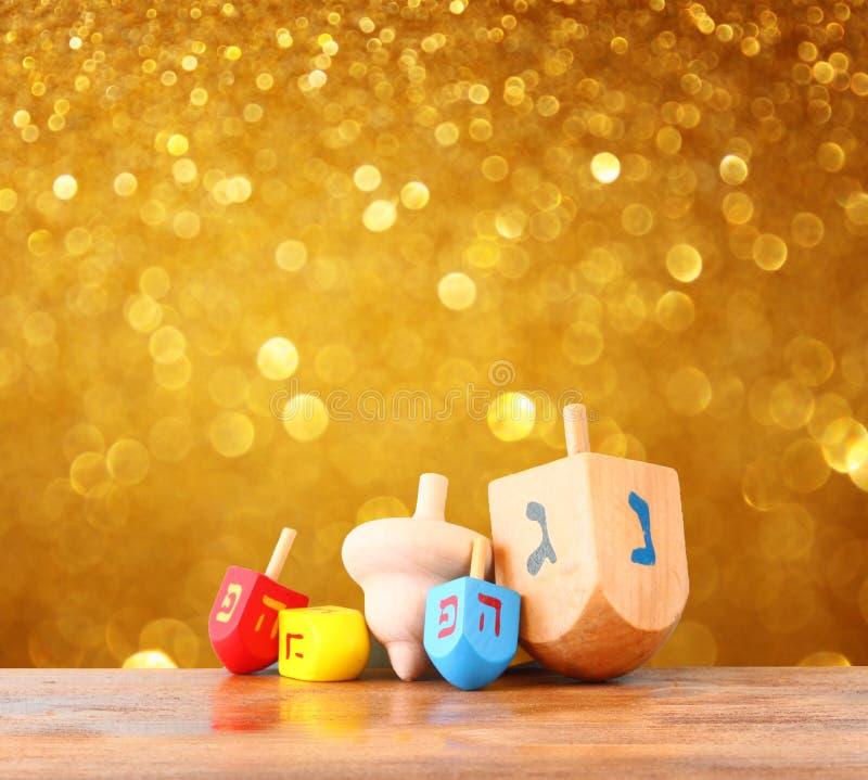 Wooden dreidels for hanukkah and glitter golden lights background royalty free stock photo