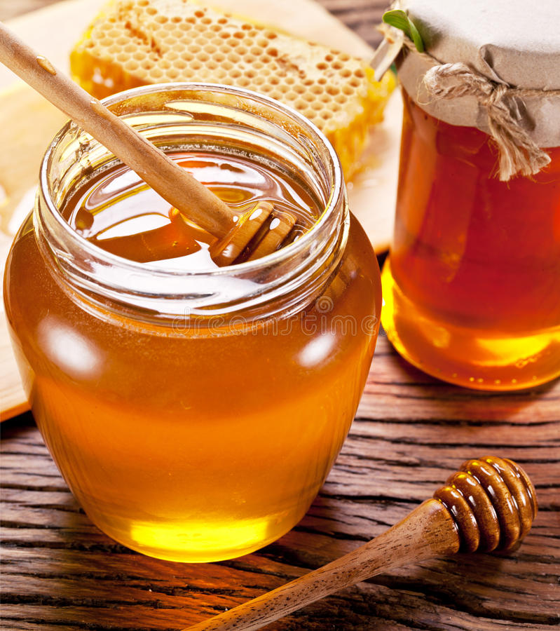Wooden dripper in glass can full of honey. Wooden dripper in glass can full of honey on wooden table stock photos