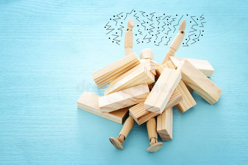 Wooden dummy buried under stack of domino blocks asking for help. concept of stress, trouble and deadline overwork. Wooden dummy buried under stack of domino royalty free stock photos