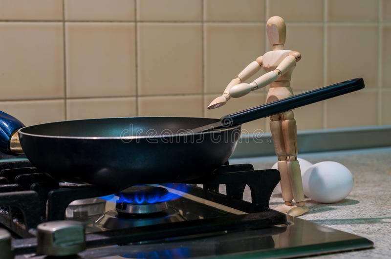 Wooden dummy, mannequin or man figurine cooking at stock photos