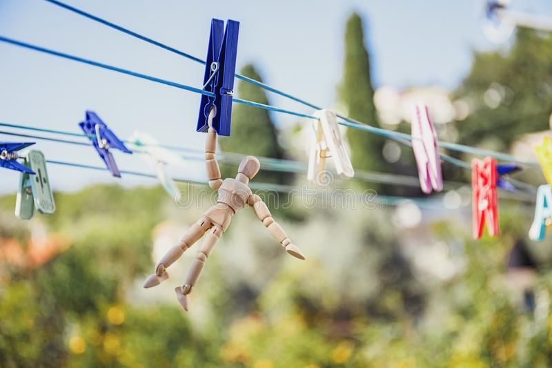 Wooden dummy puppet hanging with clothespin on clothesline. Loneliness concept. Abstract conceptual image royalty free stock photography