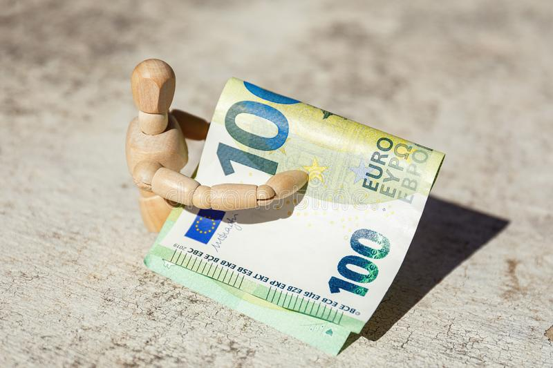 Wooden dummy puppet holding hundredth euro banknote. Business concept. Wooden dummy puppet holding hundredth euro banknote. Money or business concept. Abstract stock photography