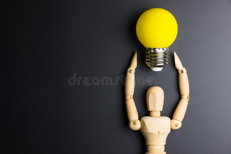 Wooden dummy toy and light bulb on black background with copy sp stock images