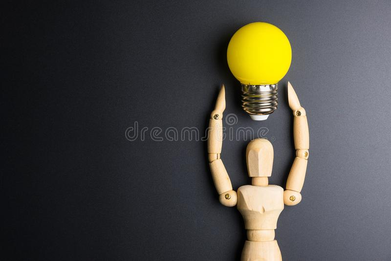 Wooden dummy toy and light bulb on black background with copy sp. Ace royalty free stock photo