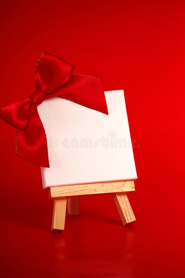 Wooden easel with blank canvas on red background royalty free stock photos
