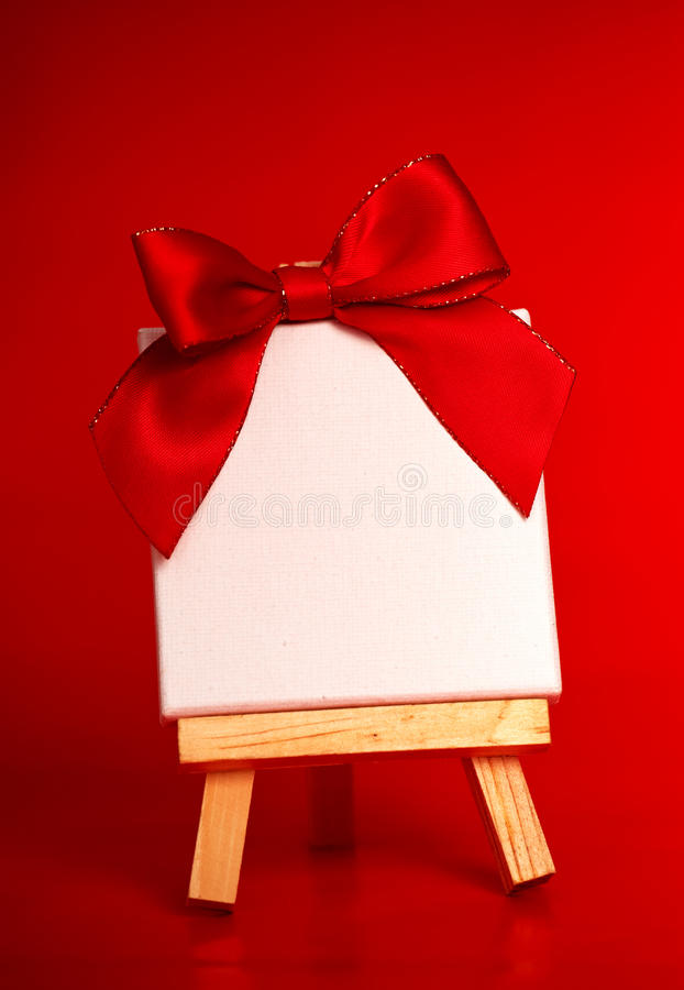 Wooden easel with blank canvas on red background royalty free stock image