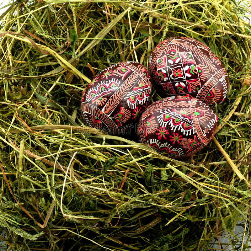 Wooden Easter eggs. Colored wooden easter eggs on straw nest royalty free stock photo