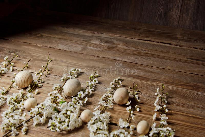 Wooden easter eggs among flowering cherry branches on a rustic table. symbolic composition of the spring holiday for a gift card. stock photo