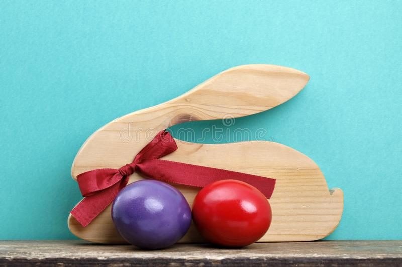 An wooden easter rabbit with red ribbon and two coloured eggs on a board. royalty free stock photography