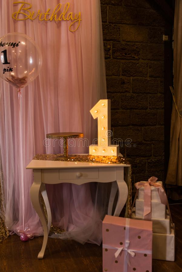 Wooden electric light up lamp alphabet in hard font on the table. Number 1. Wooden number 1 with bulbs. First birthday stock photography