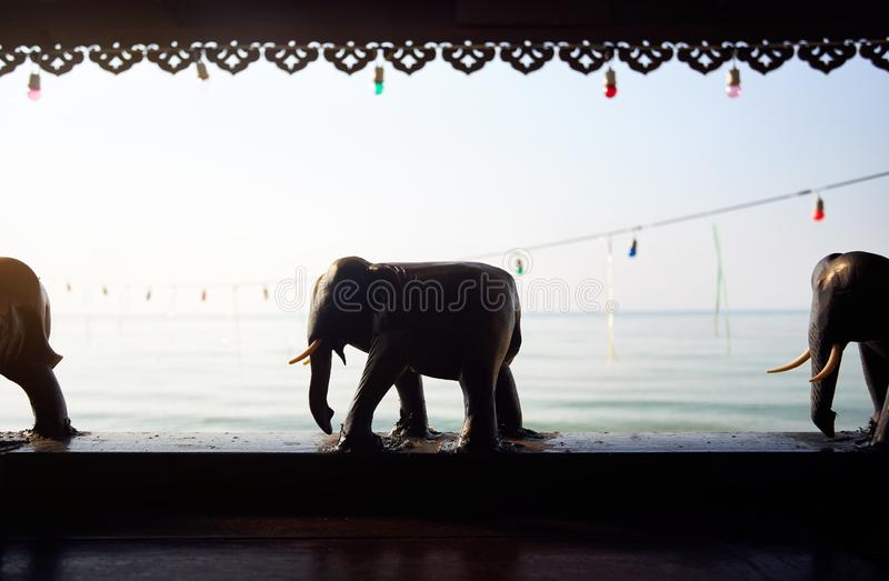 Wooden elephant statues at tropical resort. Wooden elephant statues decoration of resort at tropical beach at sunrise royalty free stock image