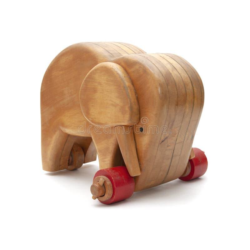 Wooden elephant with wheels on white background. Wooden elephant with red wheels on a three-quarter white background stock photo