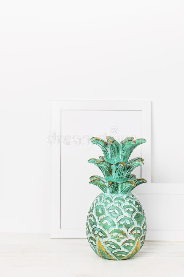 Wooden empty frames for a photo and a wooden emerald pineapple on a background of a white wall. Blank paper frames, modern home de stock photography