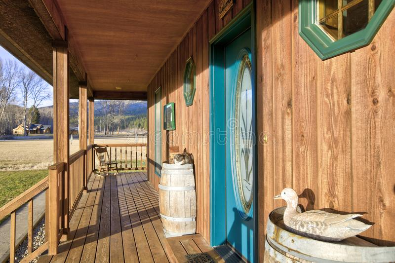 Wooden entrance porch with glass stained front door. Wooden entrance porch with glass stained front door on a sunny day. Northwest, USA stock image