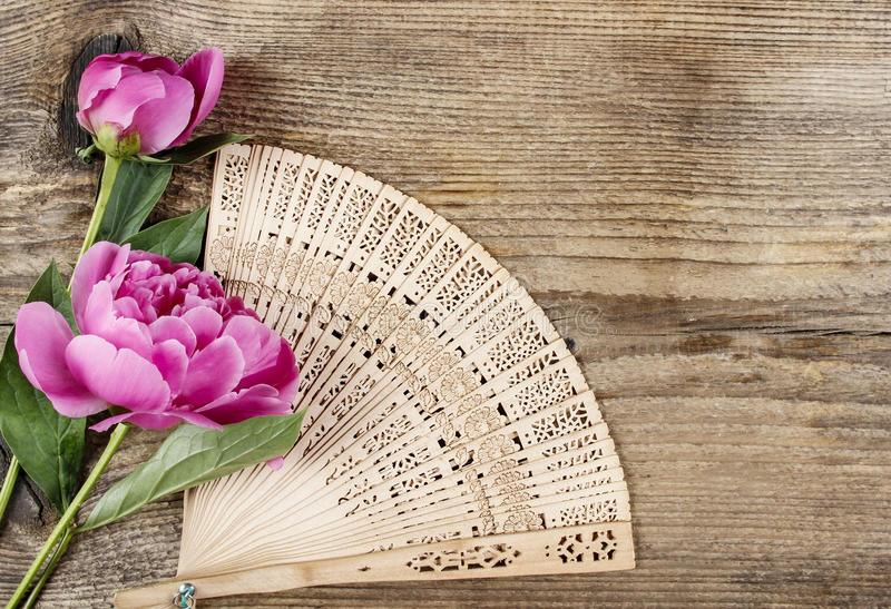 Wooden fan and pink peony on wooden background royalty free stock image