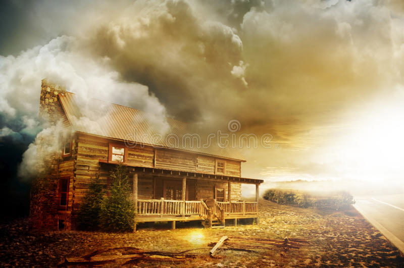 Wooden farmhouse. An old wooden abandoned farm house made of logs on a hot property with a ominous cloud coming from the west as a hot sun sets on the horizon royalty free stock photography